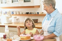 Grandmother and Granddaughter decorating a cake