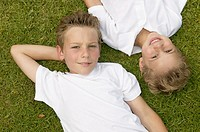 Two boys lying in the grass