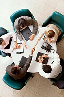 High angle view of business executives shaking hands in a meeting