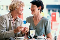 Two mature women sitting in a restaurant holding photographs