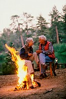 Senior couple sitting in front of a camp fire talking