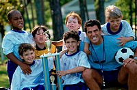 Portrait of a soccer team holding a trophy with their coach