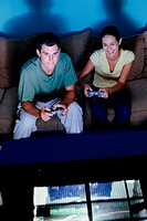 Young couple sitting on a couch playing video games