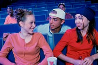 Teenage girl and a young man watching a movie in a movie theater