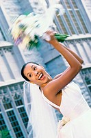 Low angle view of a newlywed young woman tossing the bouquet