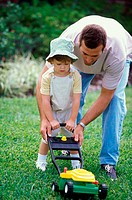 Father teaching his daughter to mow a lawn