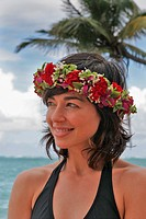 Hawaii, Oahu, Beautiful woman wearing haku lei by the ocean looks to the side.