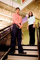 Portrait of a businessman and a businesswoman standing on stairs