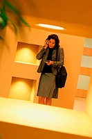 Businesswoman standing in a corridor using a mobile phone