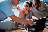Two young men and a young woman using a laptop
