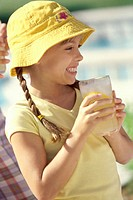 Side profile of a girl holding a glass of lemonade