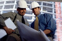 Low angle view of two foremen working on blueprints at a construction site