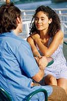 Young couple sitting face to face talking
