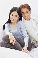 Portrait of a young couple sitting on a couch smiling