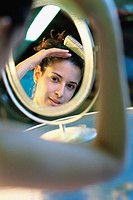 Young woman looking into a mirror