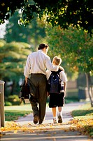 Rear view of a father walking with his son