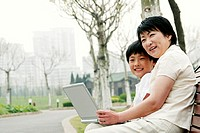 Side shot of a woman and her son sitting on the bench with a laptop on their laps.