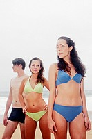 Two ladies and a guy in swimming suits standing by the beach