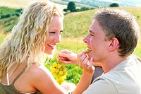 A blonde hair woman feeding her boyfriend grape