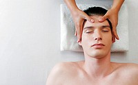 Top view of a pair of hands massaging the head of a man.