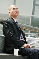 A bald man in business suit sitting on the bench holding a newspaper with a plastic cup beside him.