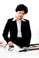 A woman in office attire ironing clothes.