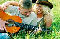 a man lying on the grass playing guitar for his girlfriend.