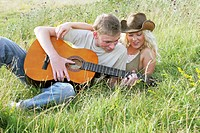 A guy playing a song on his guitar for his girlfriend.