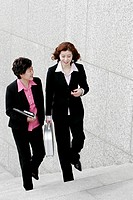 Two business women chatting while walking up the stairs.