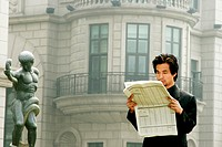 Man in business suit reading newspaper.