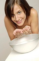 Woman flashing a smile at the camera while washing her face.