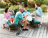 Three Generational Family Sit on Decking in Their Garden