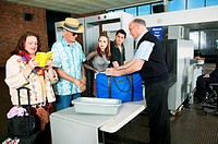Security Man Looking Examining a Man´s Luggage at an Airport X Ray Machine
