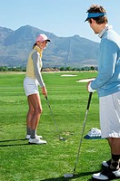 Couple Looking Face to Face on a Putting Green