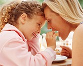 Girl (4-6) feeding mother fruit, smiling, close-up