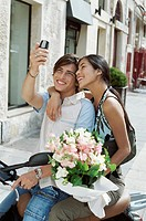 Teenage Couple Sit on a Stationary Moped Photographing Themselves on a Mobile Phone