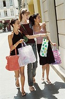 Three Friends Walk Side-by-Side Down a Pavement, Window Shopping in the Summer Sun