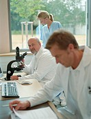 Mature male doctor by microscope in office with male doctor and nurse
