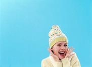 Woman wearing wollen hat, hands by face, smiling, portrait