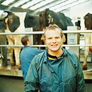 Man standing in dairy farm wearing overalls, smiling, portrait