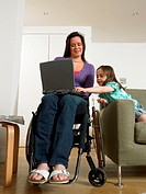 Mother in wheelchair using laptop with daughter (6-8) smiling