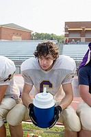 Football player takes a water break during practice