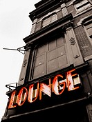 Neon restaurant sign of a lounge in New York City. The sign is in color, the rest of the photo is black and white.  Abstract camera angle, looking upw...