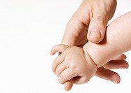 Man's hand holding baby's hand