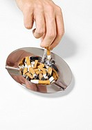 Hand putting out cigarette in ashtray
