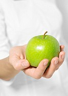Woman's hand holding out apple