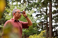 Man with binoculars in forest