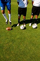 Three soccer players, two with normal balls