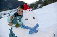 A young boy with a snowman with a Christmas had and a blue scarf