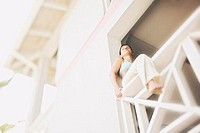 Woman Seated on White Balcony Railing